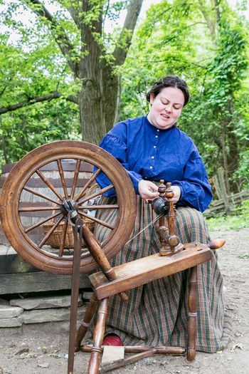 NORTH YORK, CANADA - JULY 01, 2017: A woman in her traditional dress demonstrates the traditional spinning wheel for wool yarn Ancient Antique Black Creek Pioneer Village Adult Casual Clothing Day Front View Full Length Looking At Camera Mid Adult Mode Of Transportation North York , Canada One Person Outdoors Plant Real People Sitting Smiling Transportation Tree Weaving Weaving Loom Wheel Yarn Young Adult