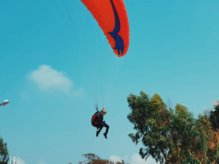 Flying !! Sky Blue Blue Sky Extreme Sports Tree Parachute Flying Headwear Sport Men Adventure Full Length Paragliding Skydiving Go Higher The Street Photographer - 2018 EyeEm Awards