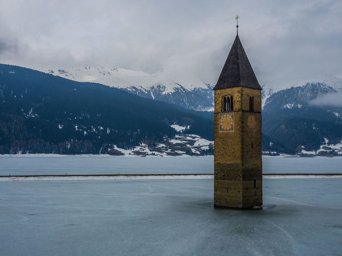 Tower in frozen lake against mountains