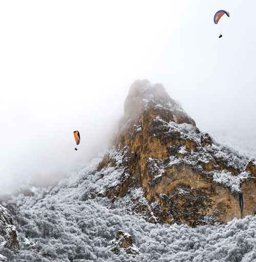 People paragliding over snow mountains against sky