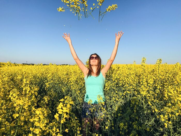 Young woman throwing yellow flowers at oilseed rape field