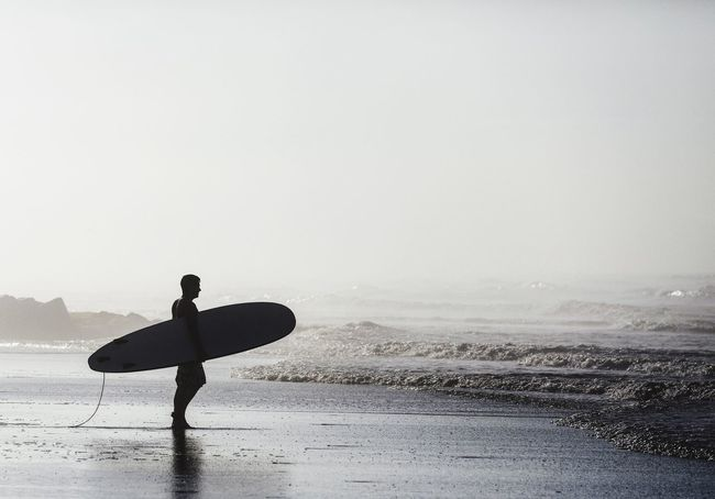 Dawn Patrol. Sea Beach Water Shore One Person Real People Surfboard Leisure Activity Lifestyles Full Length Nature Wave Men Sand Beauty In Nature Outdoors Surfing Horizon Over Water Standing Scenics