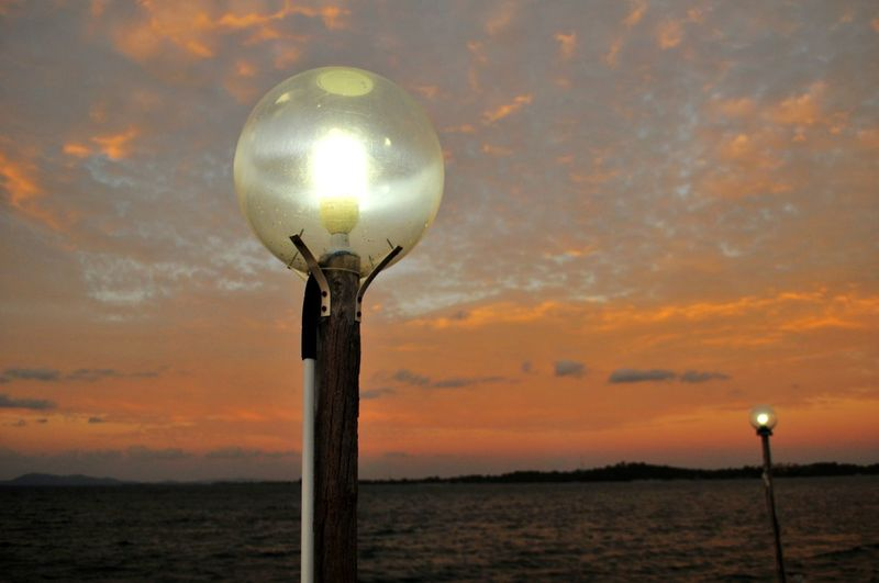 EyeEm Selects EyeEmBestPics Mood Warm Illustration Orange Sunlight Sunrise_sunsets_aroundworld Sunrise Lamp Lamp Post Sunset Beach Innovation Star - Space Silhouette Illuminated Sea Sun Dramatic Sky Moody Sky Romantic Sky
