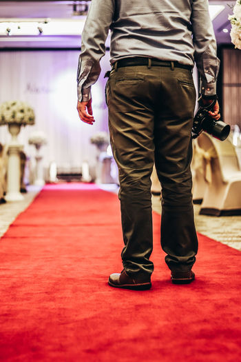 Low section of photographer standing on carpet at wedding ceremony