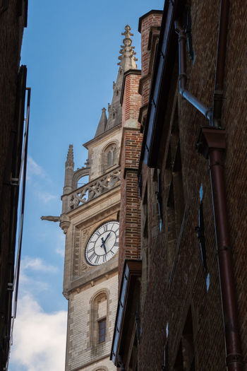 Low angle view of clock tower amidst buildings in city
