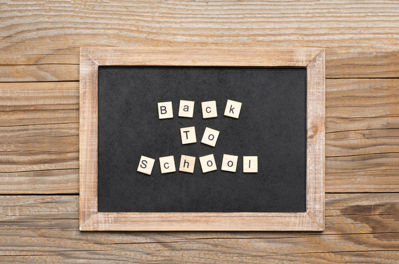 The phrase back to school written with wooden tiles on a small chalkboard against an old wooden background Alphabet Letters Rustic Text Wall Weathered Wood Aged Back To School Backgrounds Blackboard  Board Brown Chalkboard Communication Education Frame Grain Old School Table Tiles Wooden Words Written