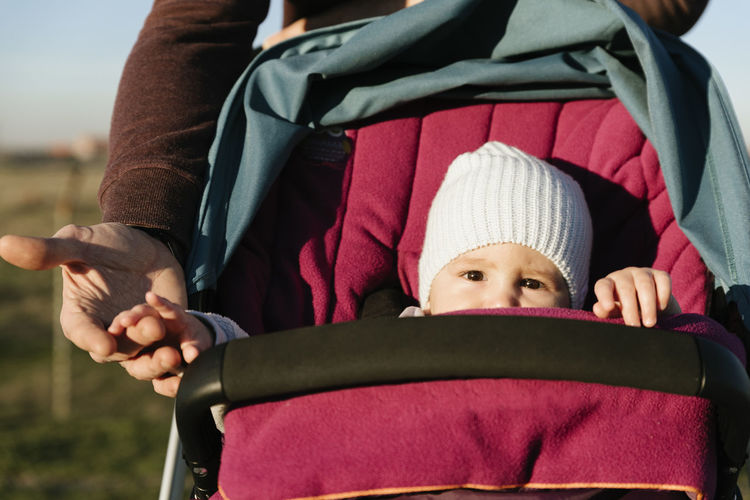 Midsection of father pushing baby in stroller