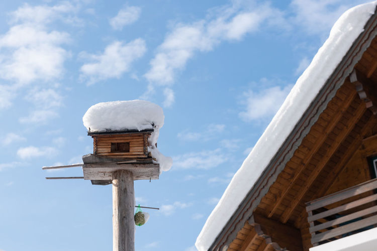 Homemade wooden bird's feeder in winter, under snow. blue cloudy sky, house at the background.