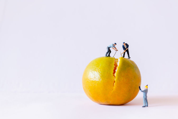 Miniature people working with orange