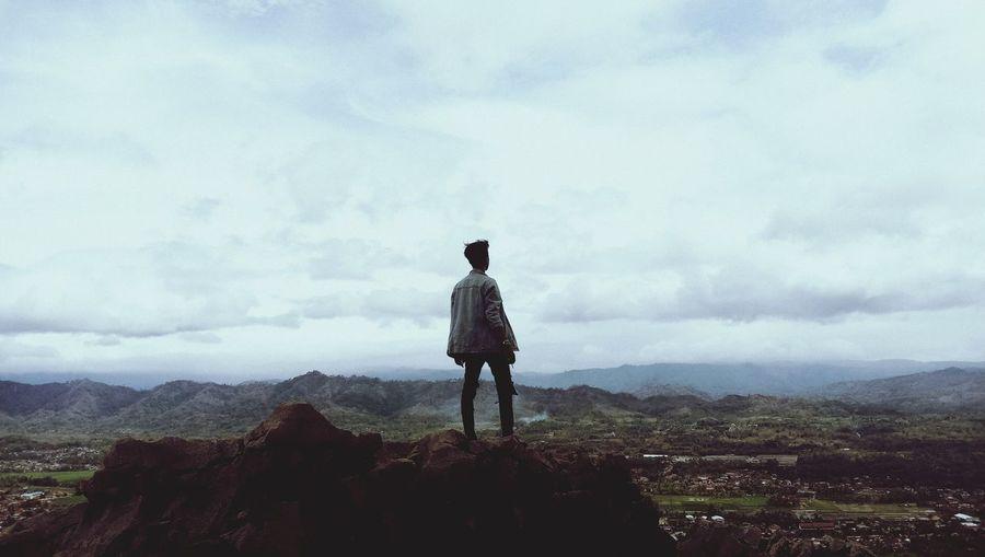 Full length of man standing on cliff