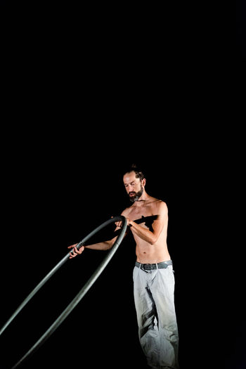 Circus Adult Black Background Casual Clothing Copy Space Holding Indoors  Jeans Lifestyles Males  Men Mid Adult One Person Shirtless Standing Strength Studio Shot Three Quarter Length Young Adult Young Men