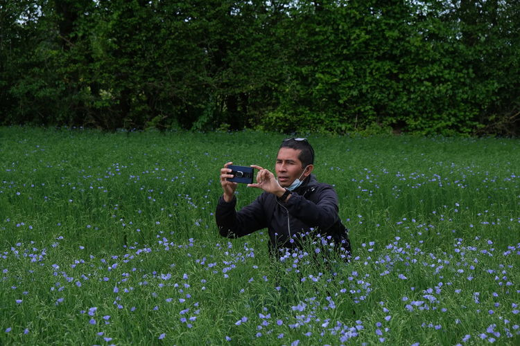 Man photographing on grassy field