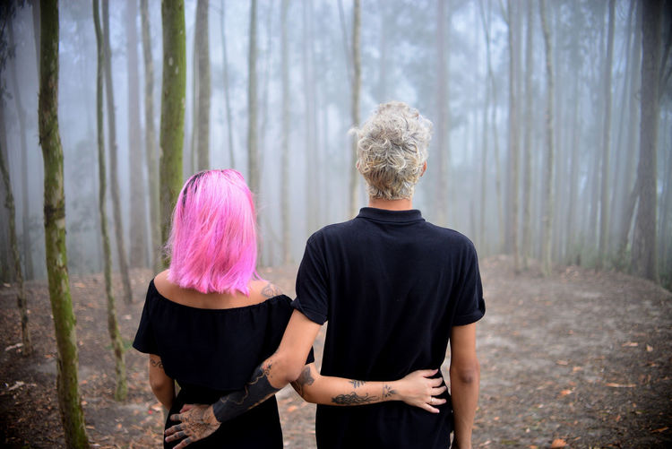 Rear view of couple standing in forest