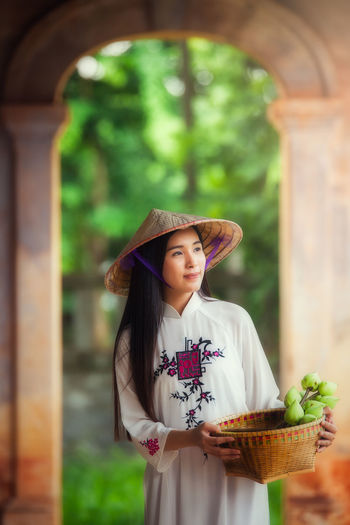 Woman dressed Vietnamese Vietnamese Architectural Column Architecture Built Structure Casual Clothing Day Dressed Focus On Foreground Front View Hat Leisure Activity Lifestyles One Person Outdoors Real People Standing Young Adult Young Women