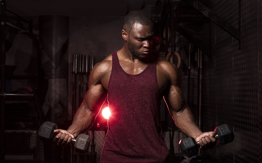 Young man exercising with dumbbells while standing in gym