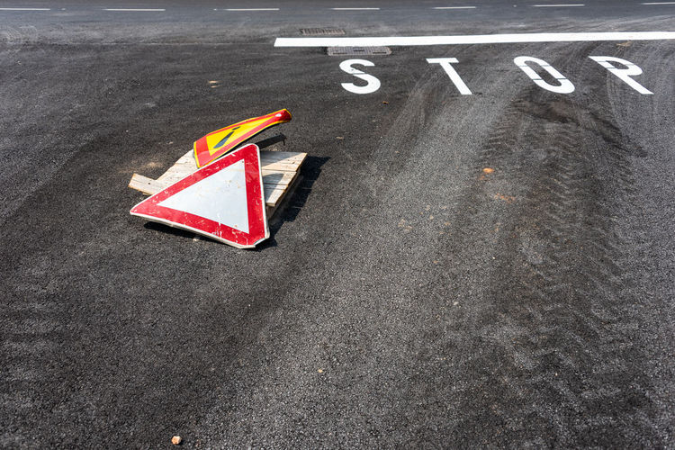 Warning signs  on asphalt road with white stop sign.