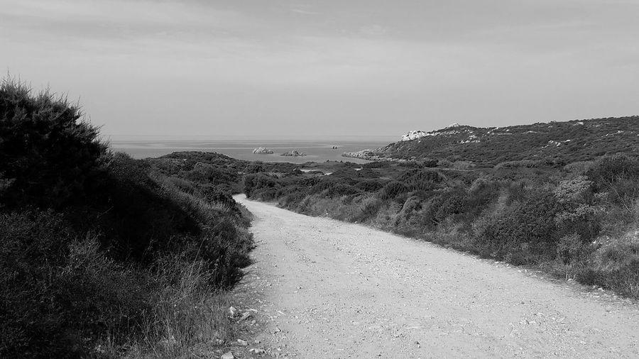 Road by sea against sky