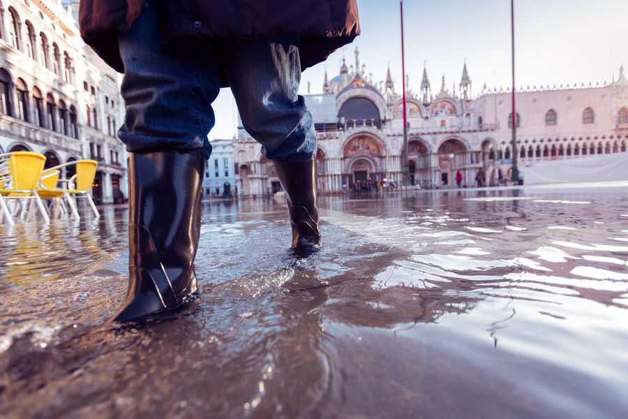 Close up of tourist's rubber boots walking through a flooded St. Mark's Square in Venice, Italy, Aqua Alta Architecture Boots Building Exterior Built Structure City Flood Flooding Human Leg Low Section Real People Rubber Boots Sky St Mark's Square St Mark's Square Venice St Marks Square St Marks Square Venice Tourism Tourist Travel Travel Destinations Vacations Venice Venice, Italy Water