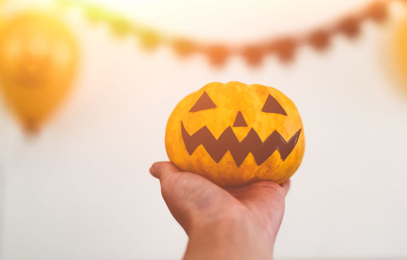 Close-up of hand holding pumpkin against orange background