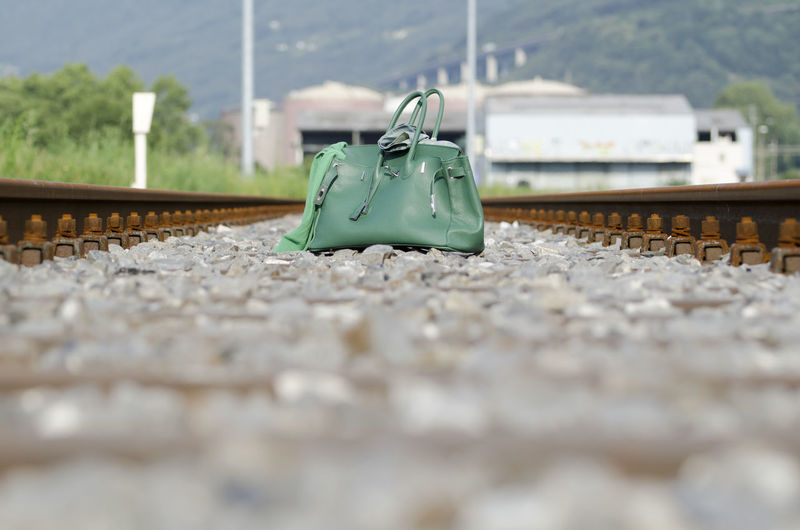 Bag on the Railroad Track Absence Bag Close-up Day Green Color Mode Of Transportation No People Outdoors Public Transportation Rail Transportation Railroad Track Selective Focus Still Life Suitcase Surface Level Track Transportation Travel