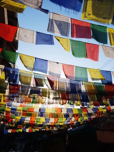 Low angle view of colorful prayer flags hanging against clear sky