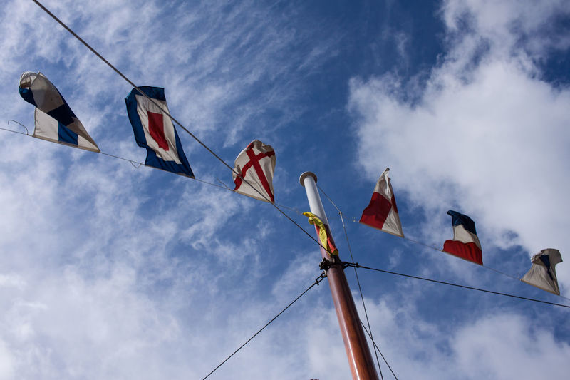 Sky Cloud - Sky Low Angle View Flag No People Day Wind Outdoors Multi Colored Hanging Blue Symbol Waving