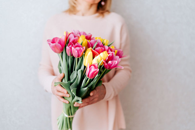 Close-up of woman holding pink tulip flower