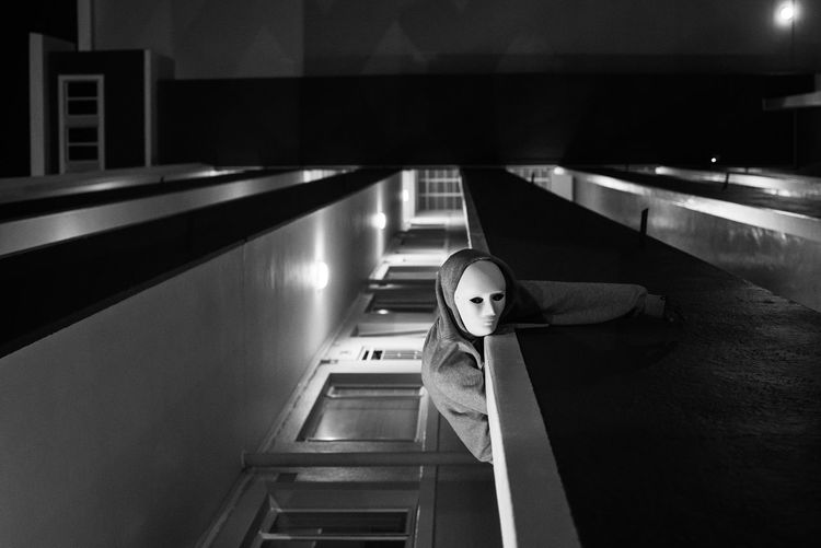 Tilt image of person wearing mask while bending in balcony at night