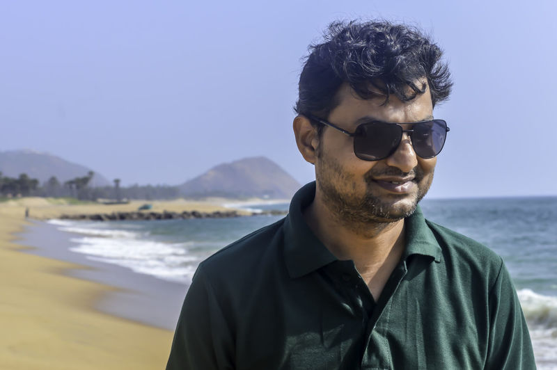 Man wearing sunglasses at beach against clear blue sky