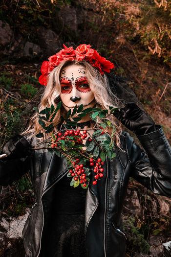 Closeup portrait of calavera catrina. young woman with sugar skull makeup and red flowers. dia de
