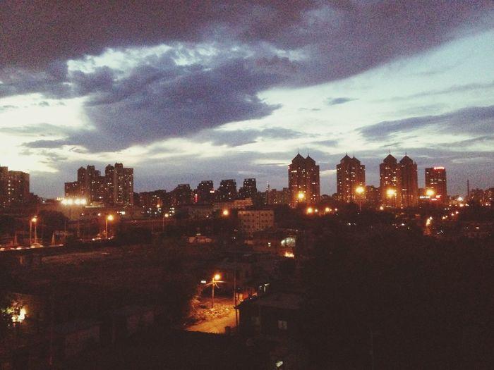 Illuminated buildings in city against sky at dusk