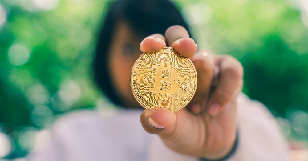 Close-up of woman holding bitcoin