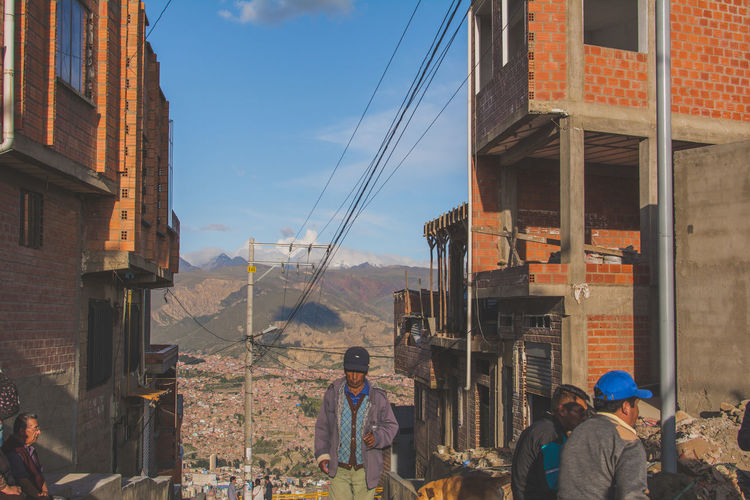 At the top of the Mi Teliferico cable car in La Paz, El Alto - Bolivia Architecture Building Exterior Built Structure Cable Casual Clothing Day In Front Of Men Person Power Line  Rear View Residential Building Residential District Residential Structure Sky