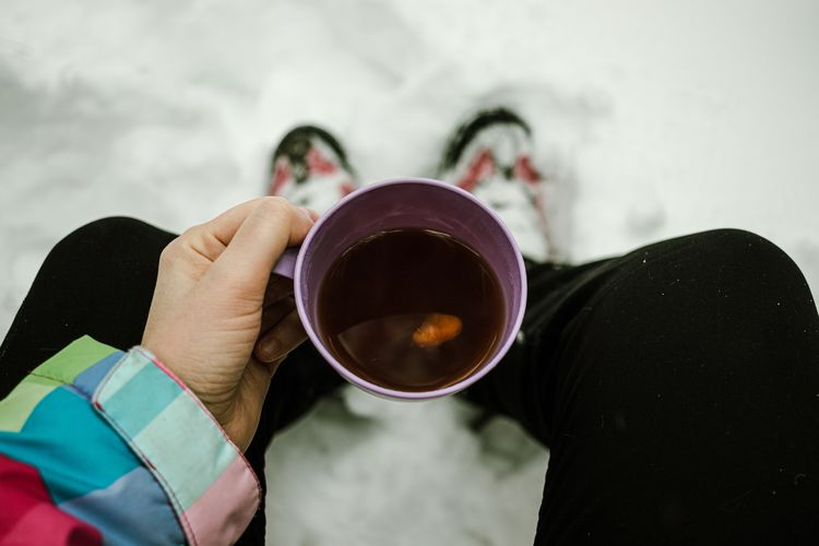 High angle view of man holding tea cup during winter