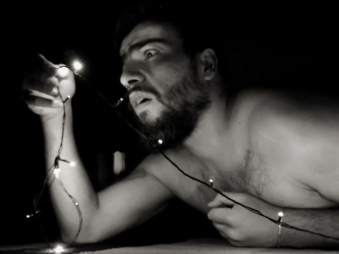 Close-up of shirtless shocked man holding illuminated string lights in darkroom