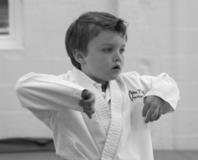 Boy in sport clothing standing at martial arts classroom