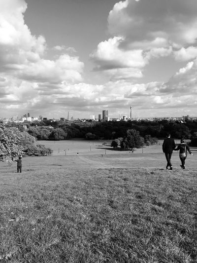 Rear view of people on primrose hill against cloudy sky