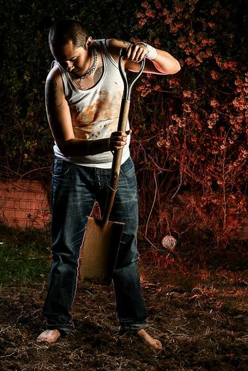 Young Man With Shovel Working In Yard At Night