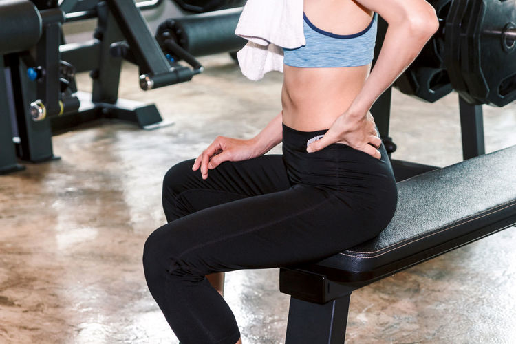 Fitness woman touching muscles of her lower back pain Adult Black Color Clothing Effort Exercise Equipment Exercising Flooring Gym Healthy Lifestyle Human Leg Indoors  Leisure Activity Lifestyles Low Section One Person Real People Seat Shorts Sitting Sport Sports Training Weight Training  Women