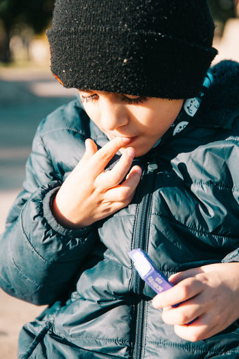 Boy wearing warm clothing and eating candy
