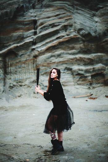 Full length of woman holding baseball bat standing outdoors