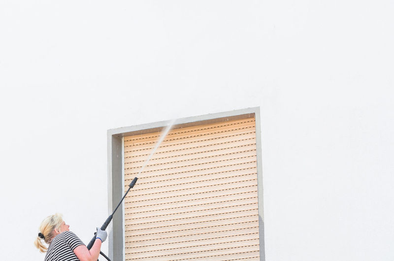 Low Angle View Of Woman Spraying Water On Wall
