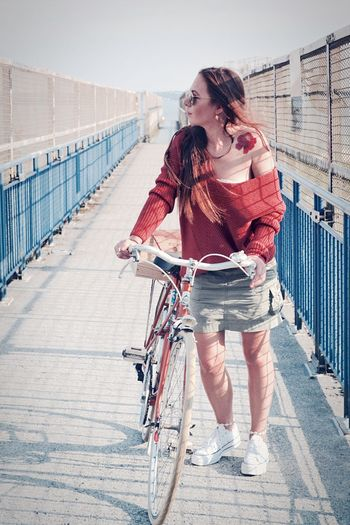 Full length of woman with bicycle standing on bridge