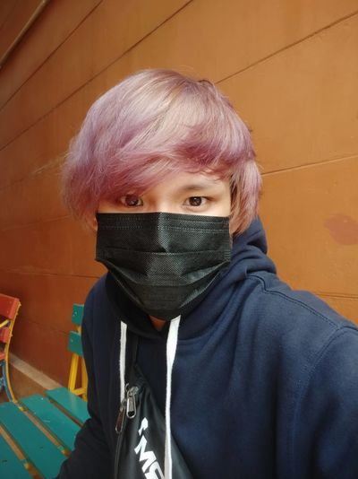 Portrait of young man with dyed hair wearing mask against wall