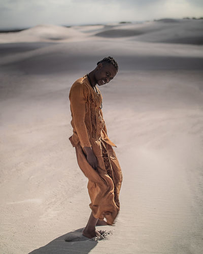 Full length portrait of young man wearing traditional clothing standing at desert