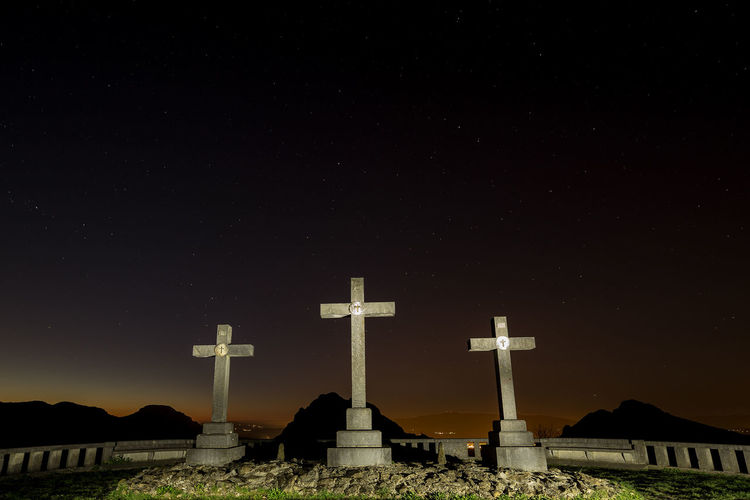 Low angle view of cross amidst buildings against sky at night