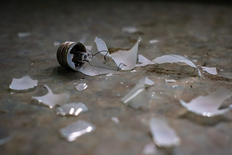 Close-Up Of Broken Light Bulb On Floor
