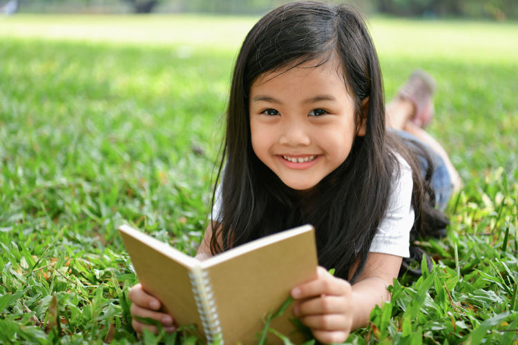 Portrait Of Smiling Girl Reading Book While Lying On Grassy Field At Park