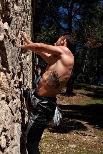 Side view of shirtless man on rock