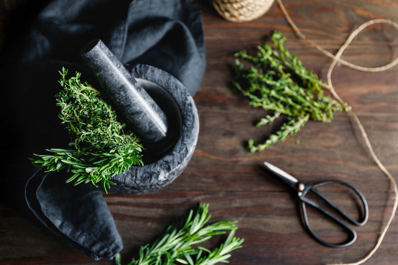 High angle view of mortar and pestle with herbs on table